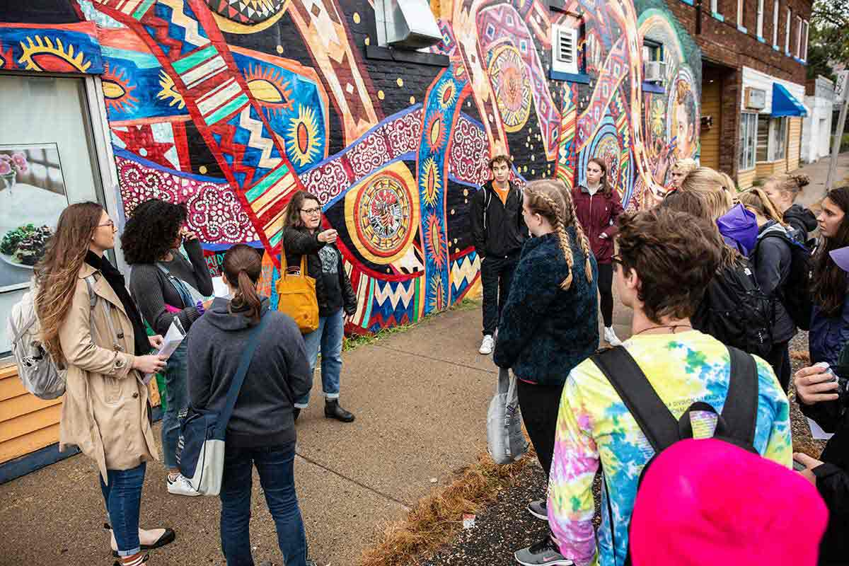Dr. Heather Shirey teaches an art history class in front of a mural in the Midway neighborhood of St. Paul.