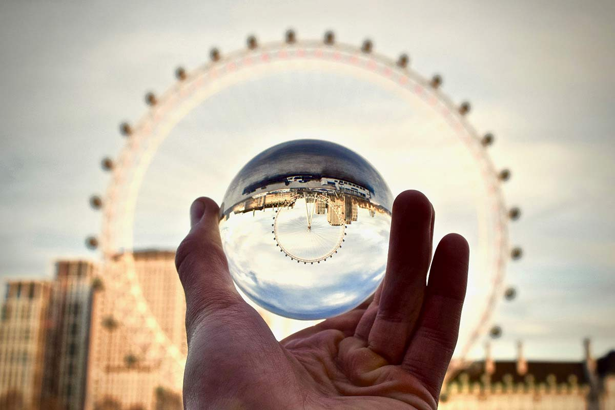 A St. Thomas student holds a looking glass up to reflect the London Eye.