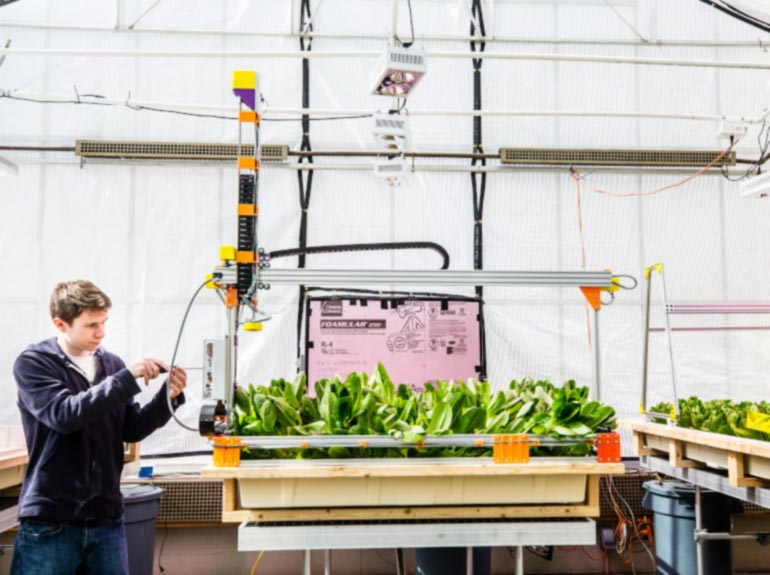 A student works on a robotic farming tool in the greenhouse.
