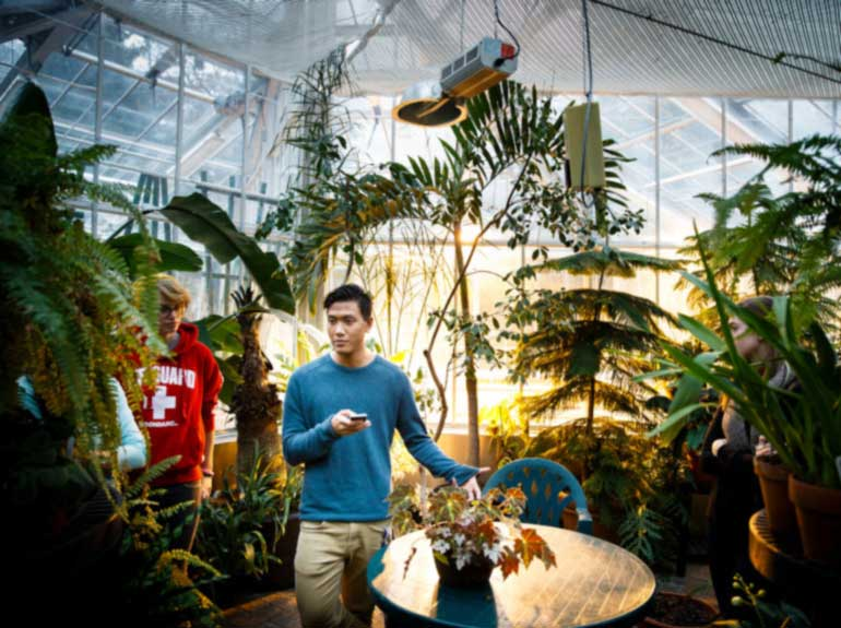 A student talks to their classmates during a biology class in a greenhouse.
