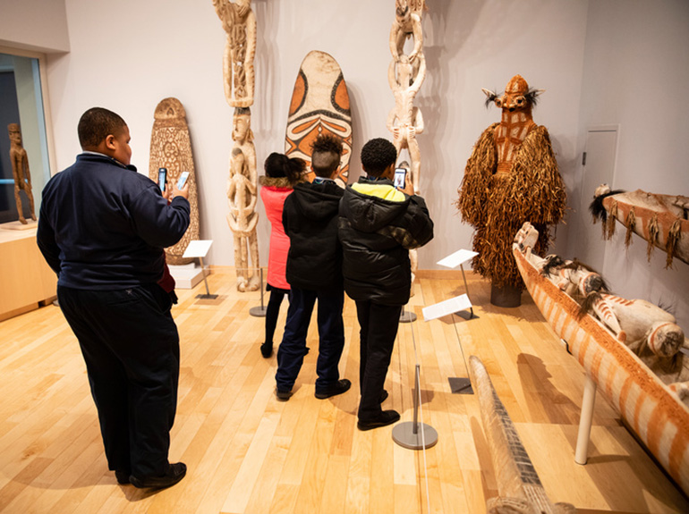 A group of children take pictures of artifacts in the Asmat Museum.