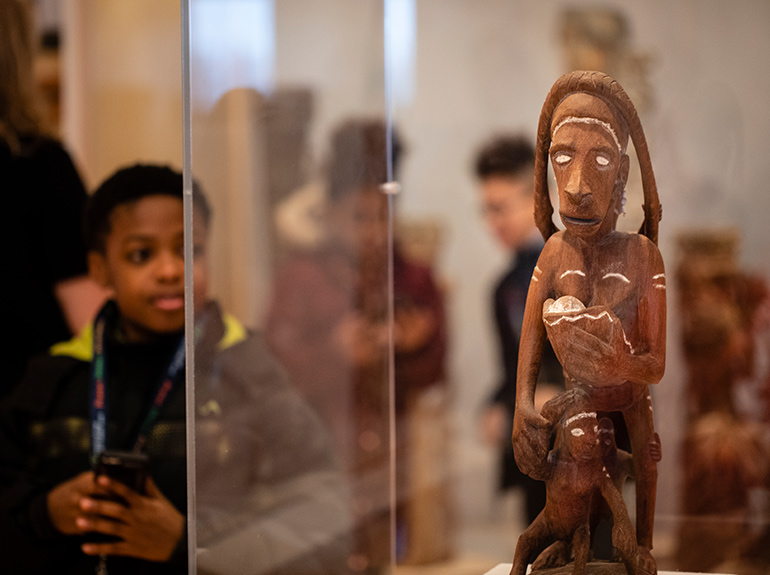 A child looks at a display during a visit to the Asmat Art Gallery.