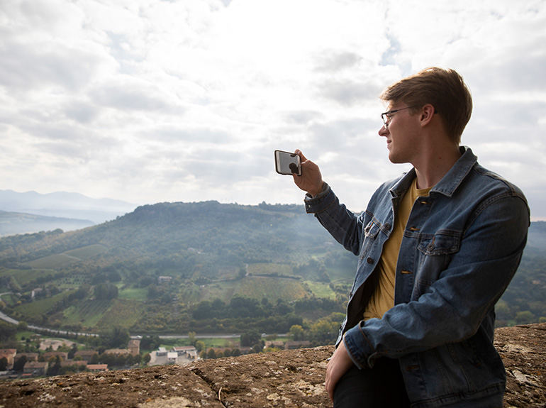 A student taking a picture with a cell phone of the Italian countryside.