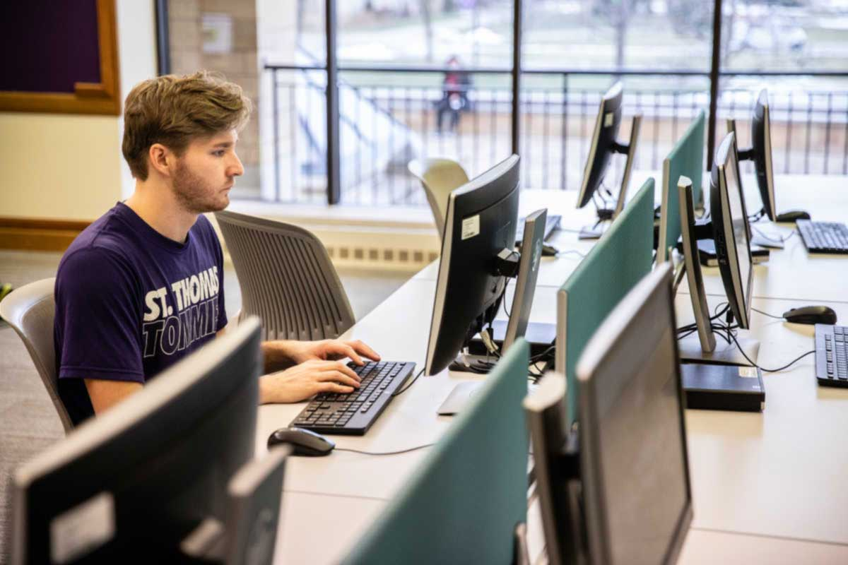 St. Thomas student working on computer in library