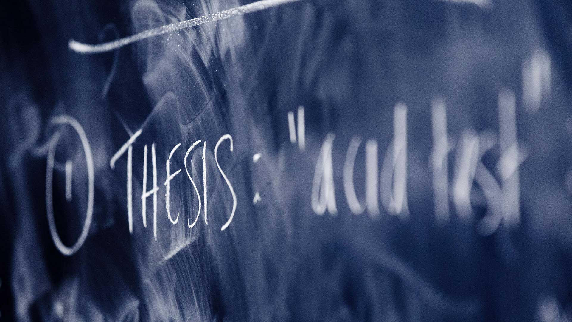 "The word ""thesis"" written on a chalkboard"