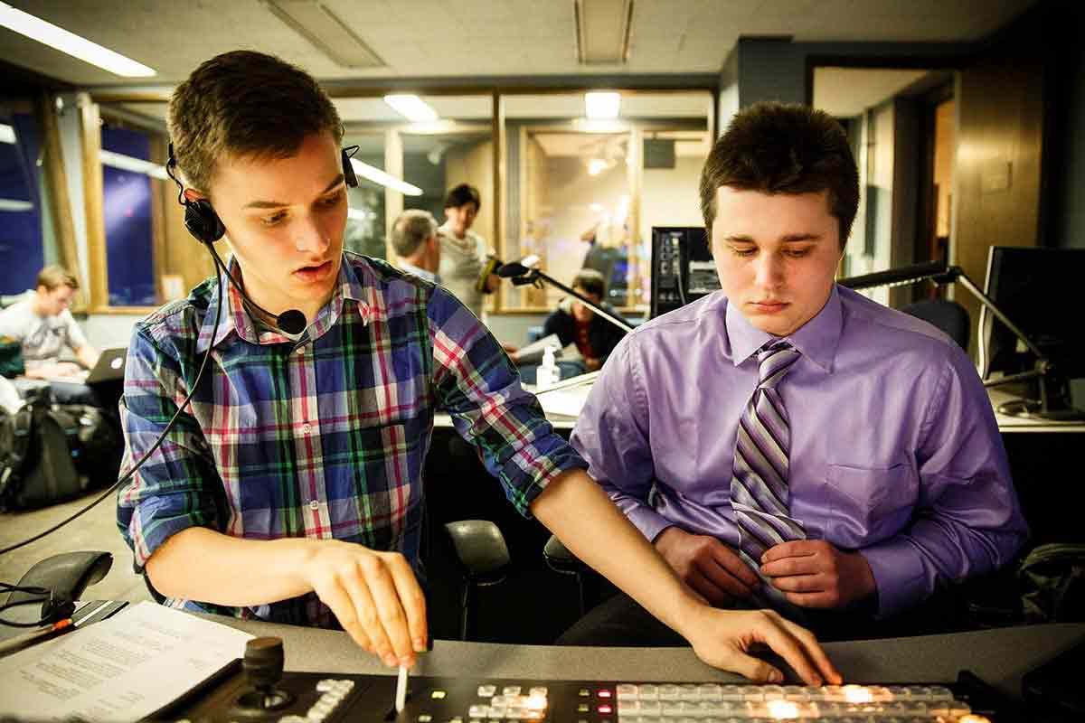 Two students operate a camera switching board in a media studio.
