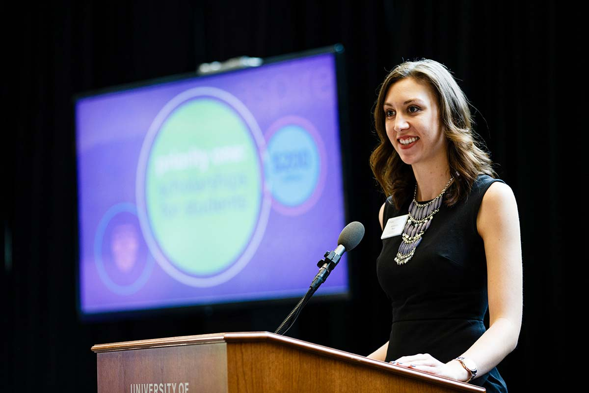 Alumna Amanda Post speaks at a podium during a scholarship presentation.