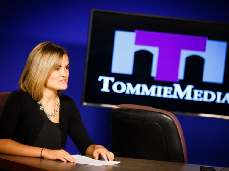 A student speaks into a camera on set for Tommie Media.