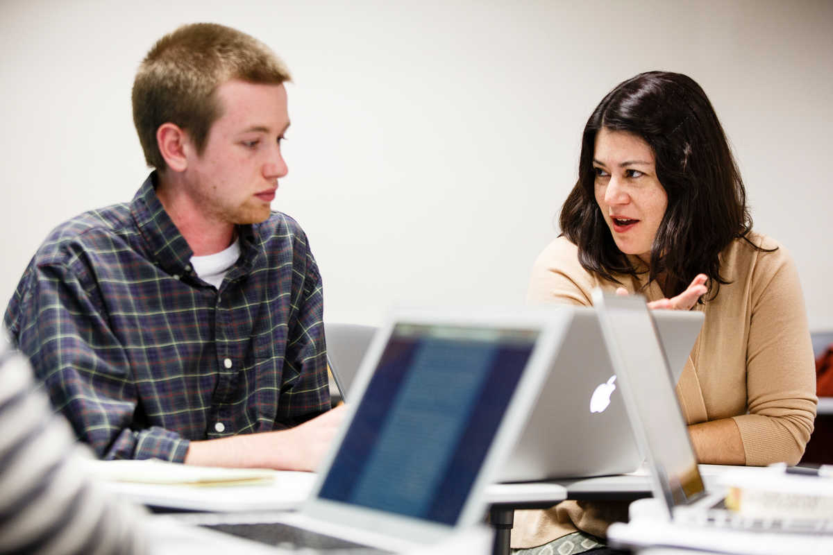 A student talks with Olga Herrera in a graduate English class.