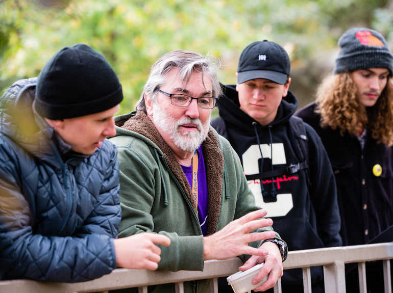Professor Thomas Hickson talks with students outdoors