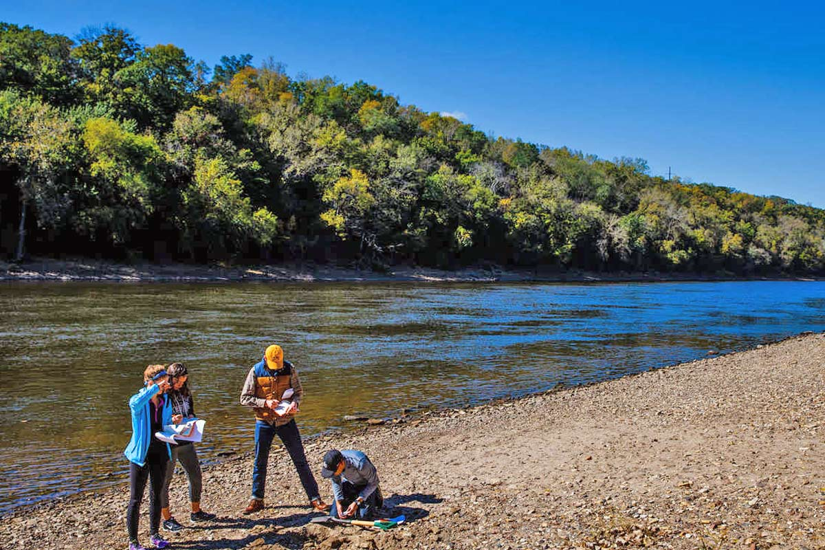 Students in the Sustainability LLC work together on a project by the Mississippi River.