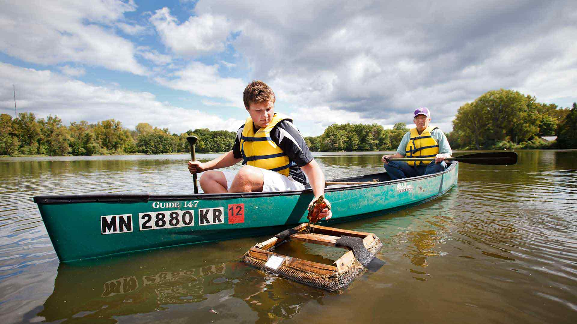 A student and faculty member examine a turtle from a canoe in a river.