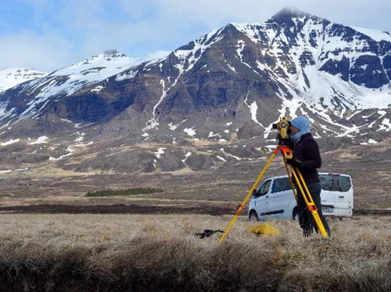 A student examines a landscape in Iceland with a mountain in the background.