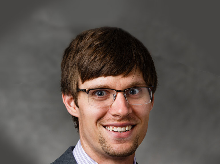 Studio headshot of economics professor Dr. Tyler Schipper.