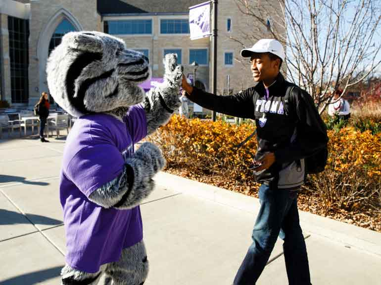 The St. Thomas mascot, Tommie, high-fives a student as they walk into the Anderson Student Center.