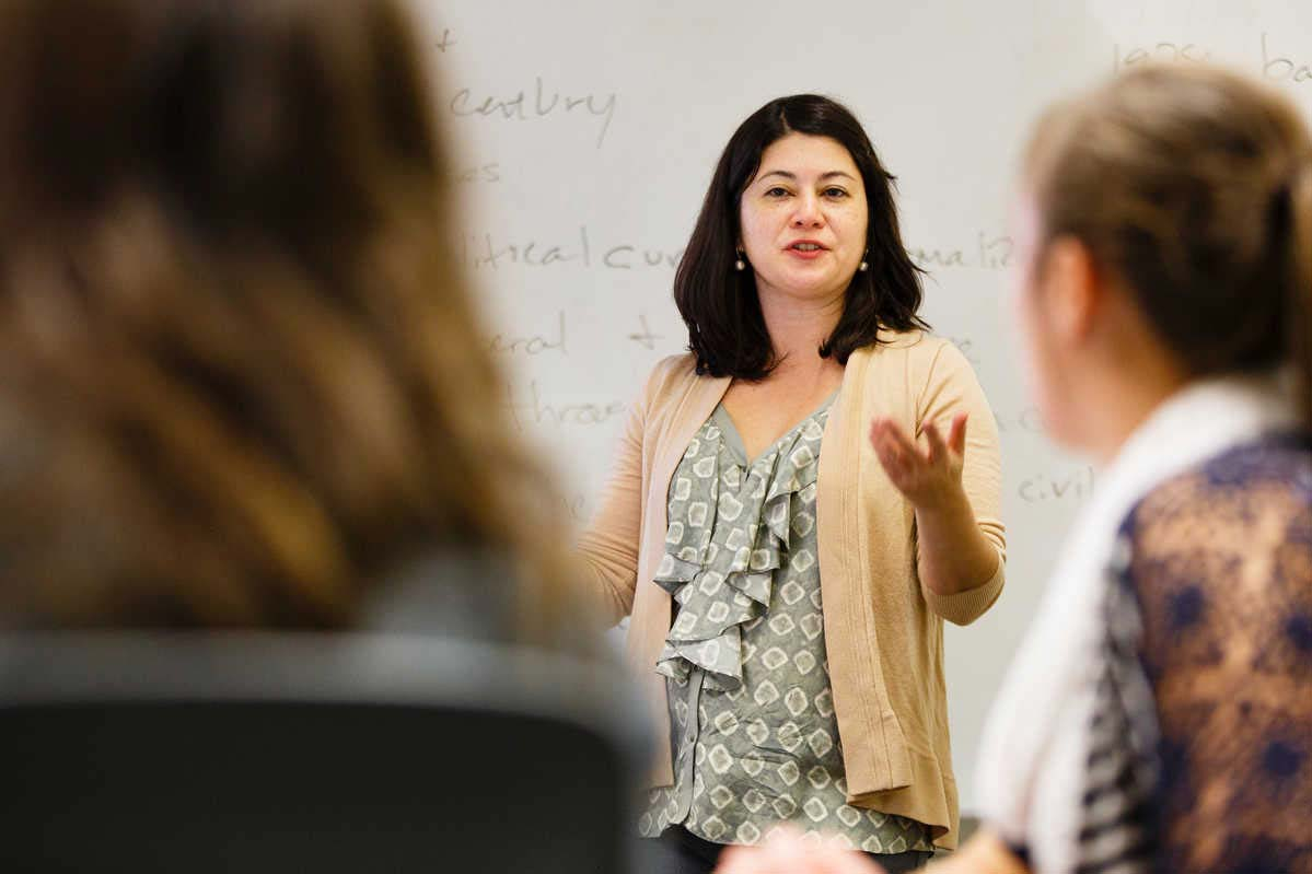 Dr. Olga Herrera leads classroom discussion in front of a whiteboard.