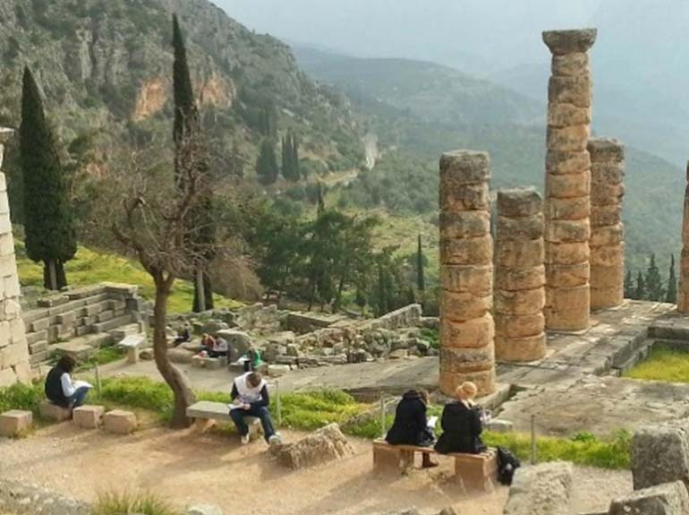 Students sit and write at ancient ruins in Greece.