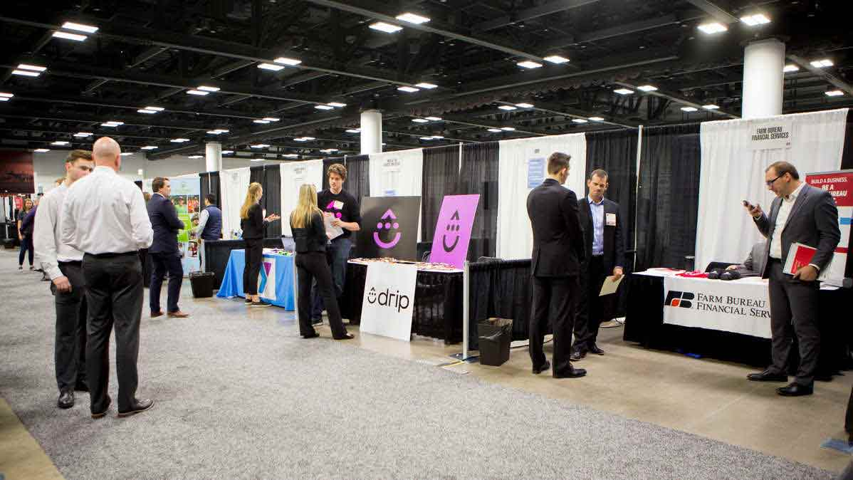Two students speak with recruiters at the Minnesota Private Colleges Job Fair.