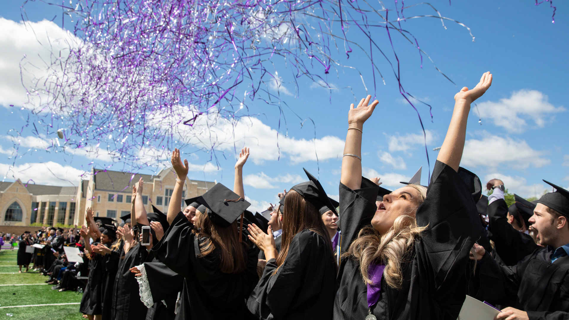 Students celebrate as confetti falls during Commencement