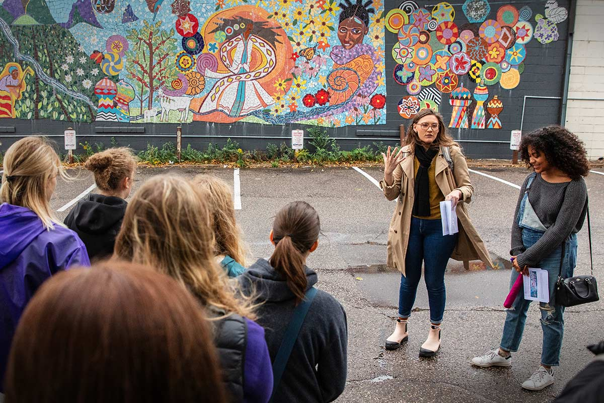 A teacher addressing a group of students in front of a mural.