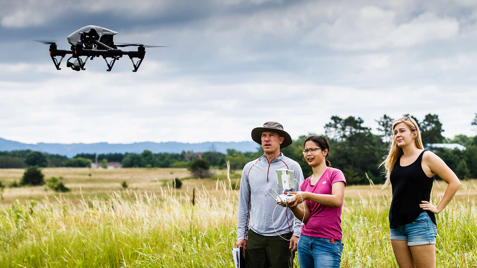 Professor and two students conduct research with the help of a drone in a field.