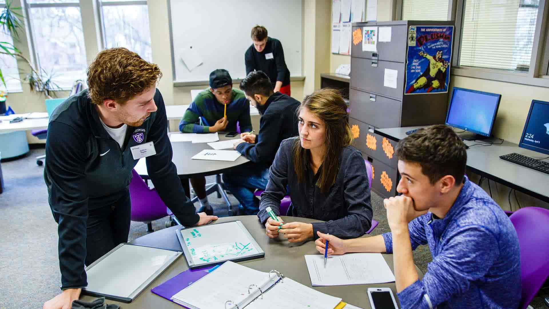Students talk around a table in the Mathematics Resource Center.