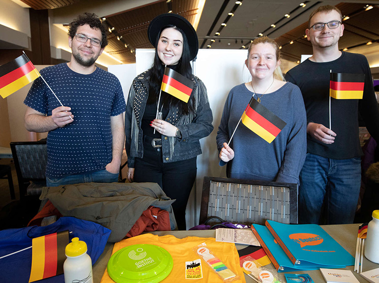 Members of the German Club pose for a photo holding tiny German flags at the Spring Activities Fair.