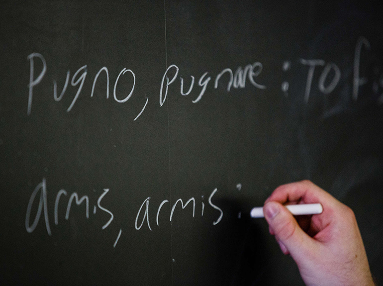 Student writing in Latin on a chalkboard.