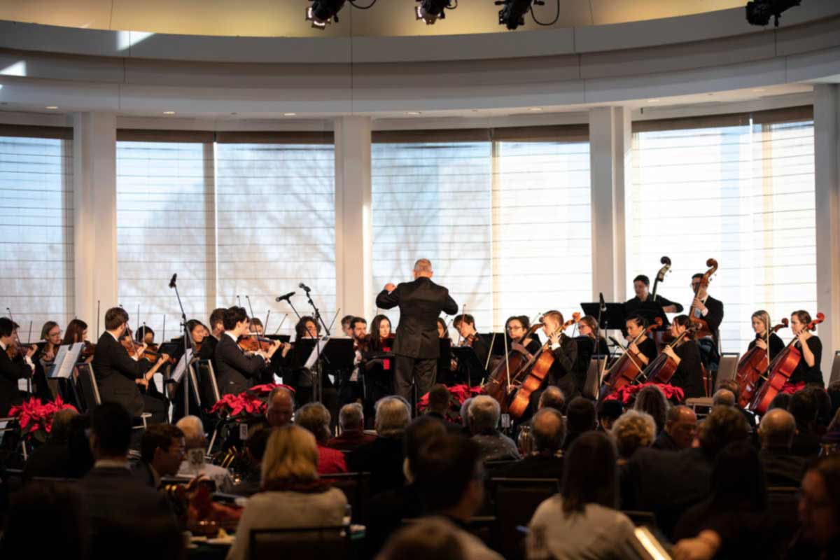 Matthew George conducts the St. Thomas String Orchestra during the First Friday Alumni Christmas Luncheon.
