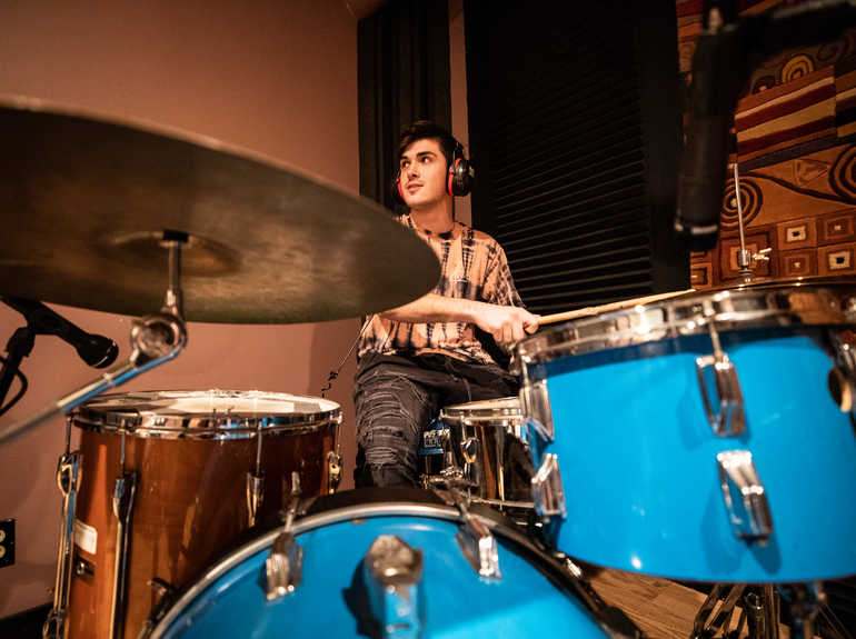 A student plays drums in a recording studio.
