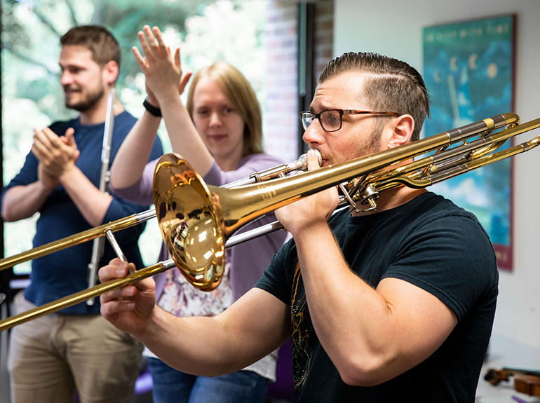 Photo of students in a graduate instrumental class performing together, with a student in the foreground playing the trombone.