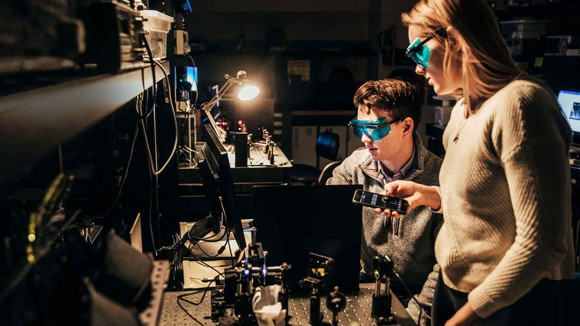 Two students work on a project involving lasers in a lab.