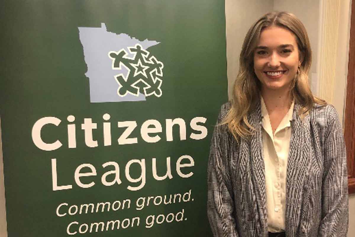 Photo of St. Thomas student Morganne DeGroot posing in front of a Citizens League banner.
