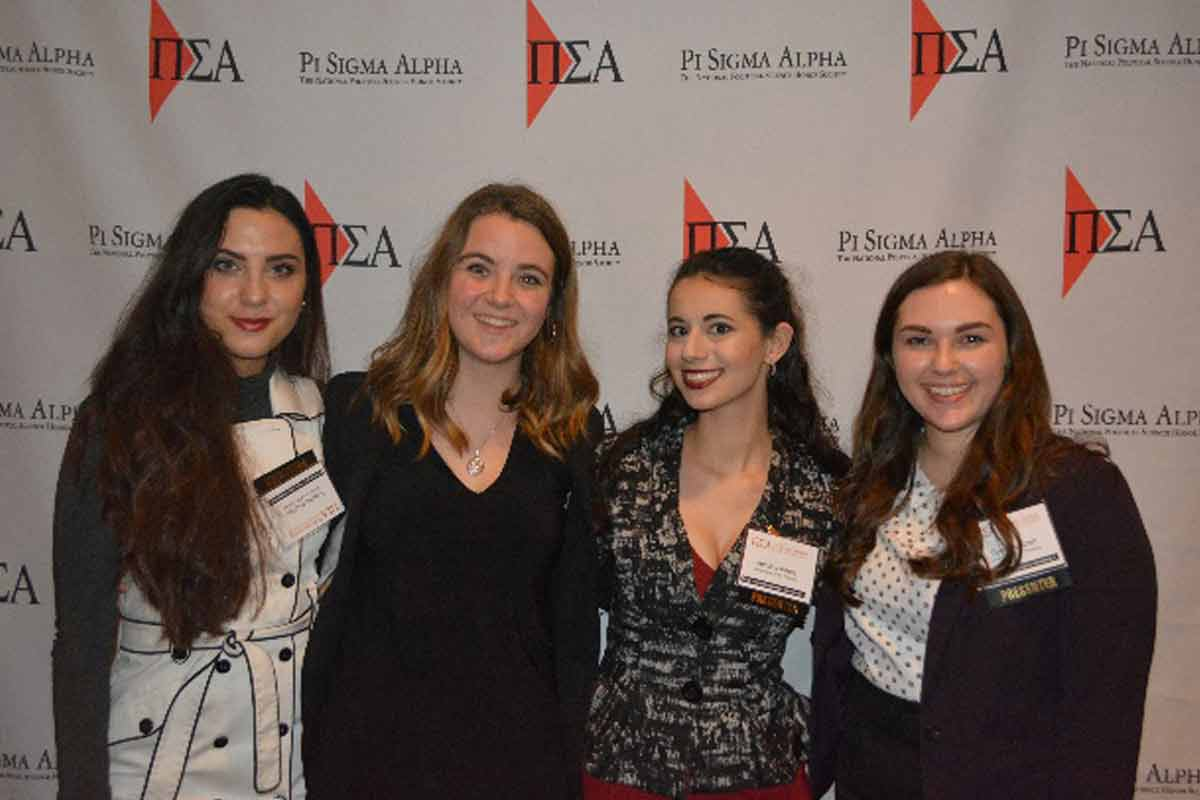 Four students pose for a photo in front a Pi Sigma Alpha Research Conference banner.