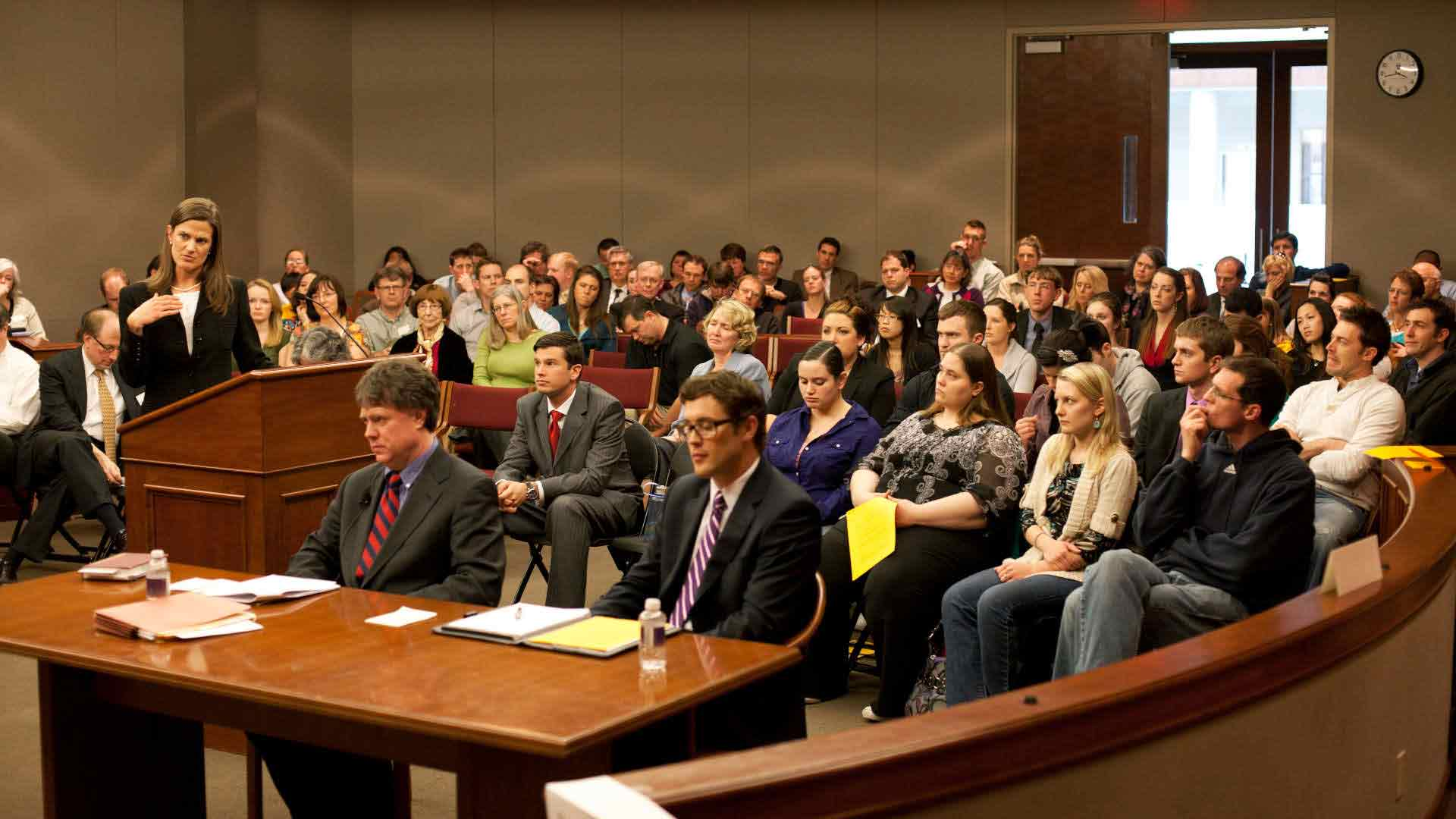 Environmental photo of a group sitting in a courtroom during a mock trial.