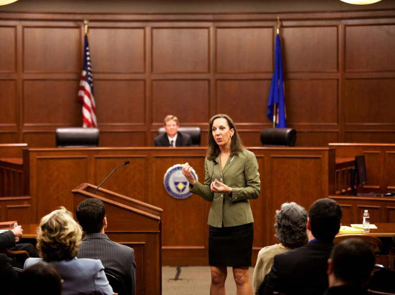 A woman speaks in front of a courtroom during a mock trial.