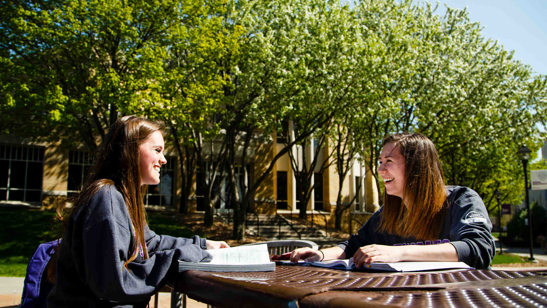 Two students sit and chat at a picnic table on a sunny day.