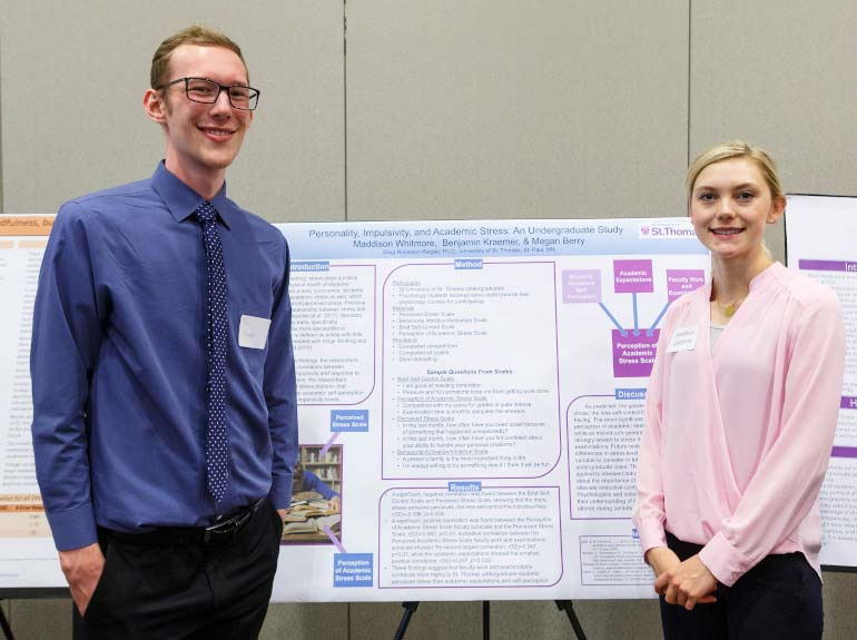 Students pose in front of their poster during the Undergraduate Research Poster Session.