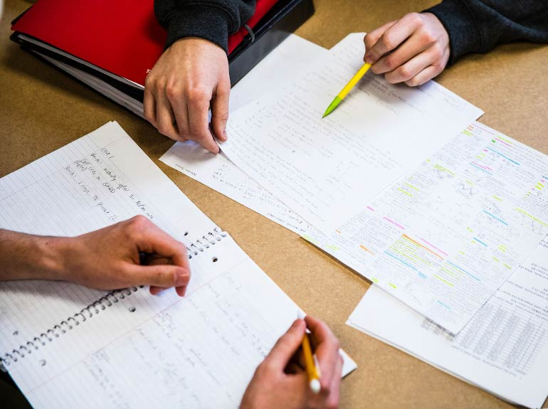 Students look over papers during a tutoring session.