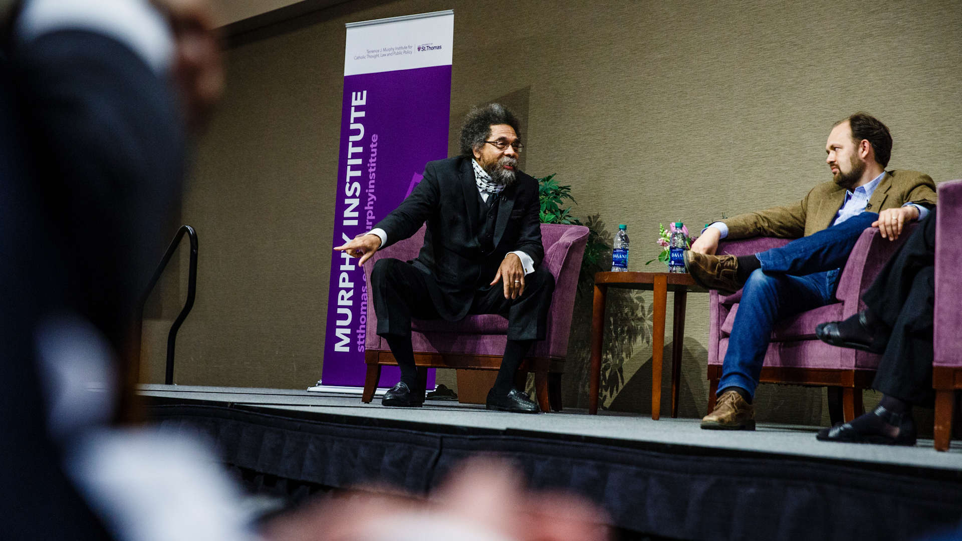 Cornell West and Ross Douthat talk during a panel discussion.