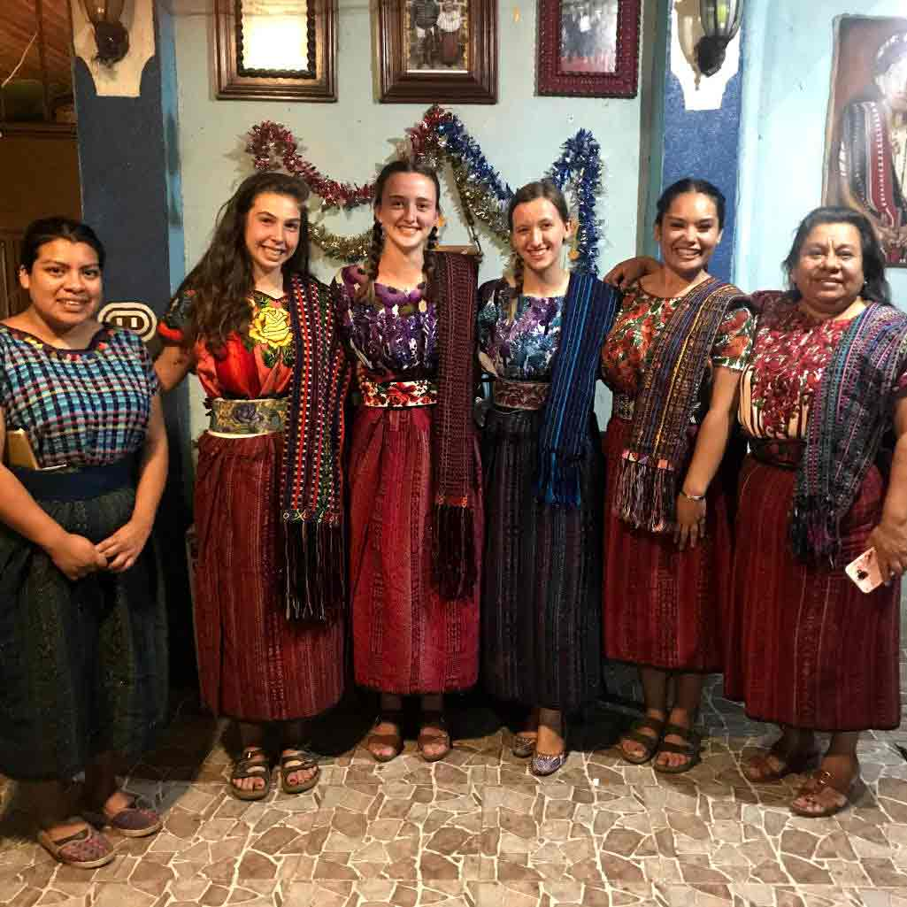 Photo of St. Thomas students posing with residents of a Guatemalan village in traditional Guatemalan dress.