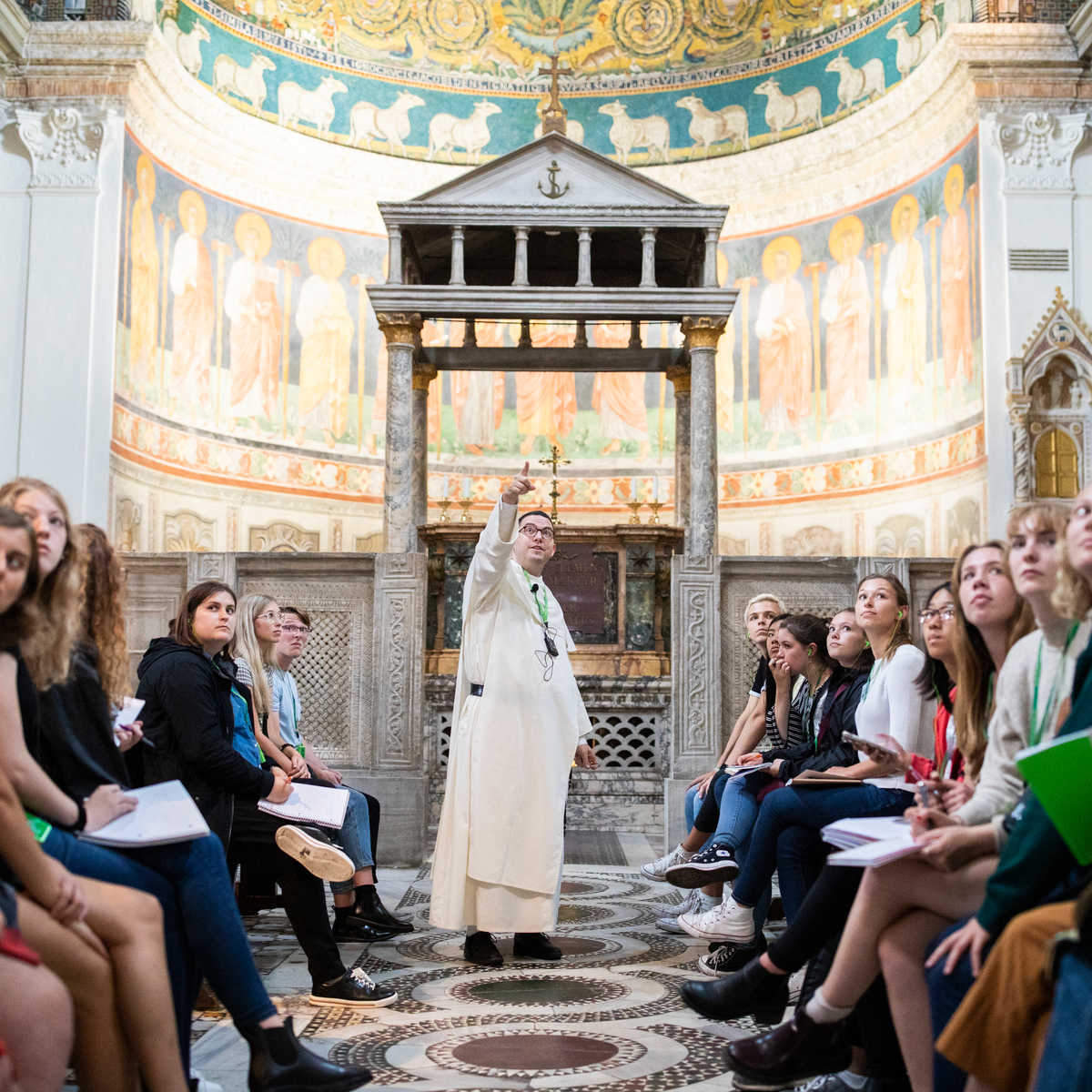 A speaker points to a piece of artwork as students listen intently in a basilica in Rome, Italy.