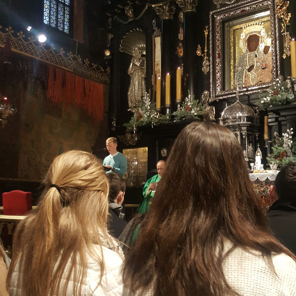 "A St. Thomas student speaks at a lectern during Mass before the ""black madonna"" in Jasna Gora monastery, Częstochowa."