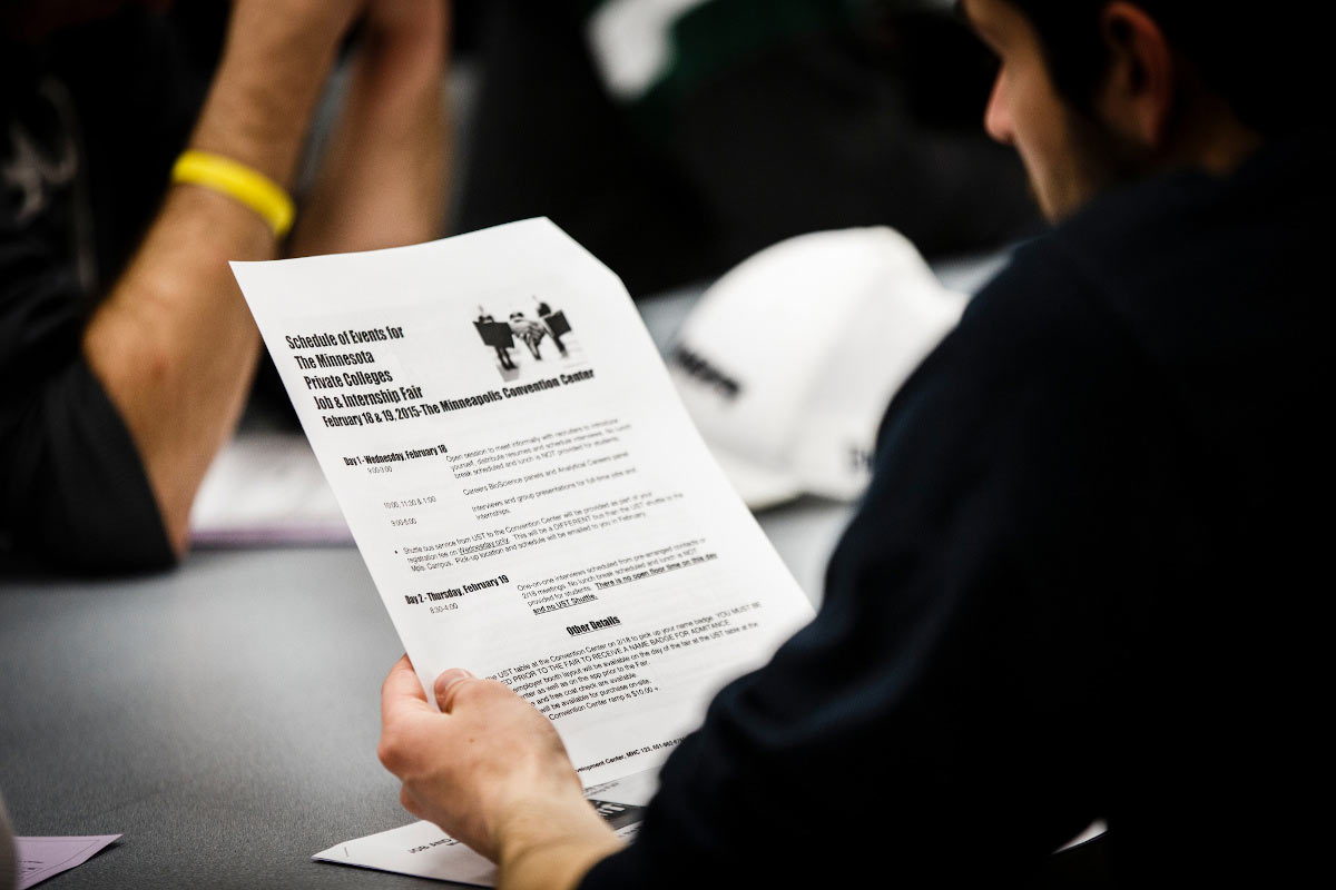 A student looks over an itinerary for the Minnesota Private College Job Fair as part of a Career Development Center seminar.