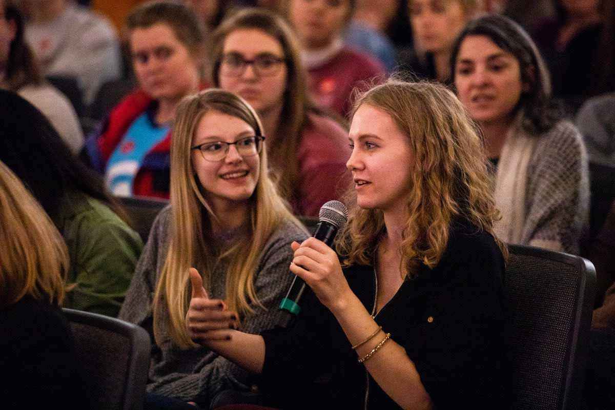 A female student holds a microphone and asks a question during an event on the St. Thomas campus hosted by the Luann Dummer Center for Women.